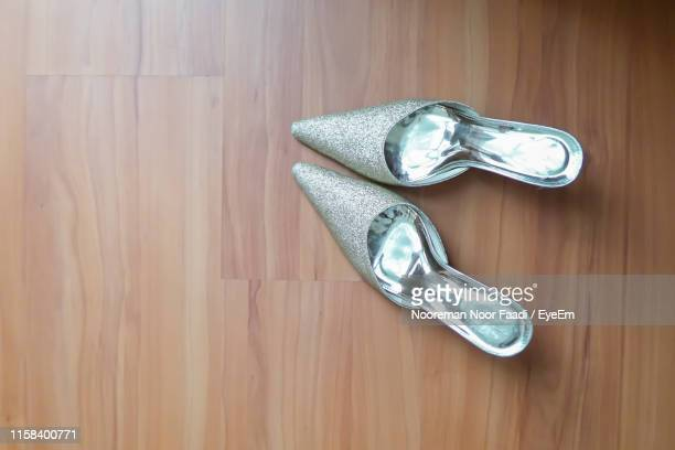 directly above shot of high heels on hardwood floor - silver shoe stock pictures, royalty-free photos & images