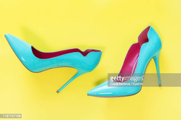 directly above shot of high heels over yellow background - stiletto stock pictures, royalty-free photos & images