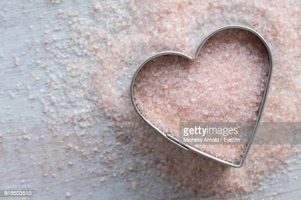 Directly Above Shot Of Himalayan Salt In Heart Shape Container On Table