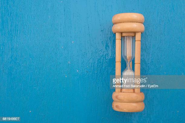 Directly Above Shot Of Hourglass On Blue Wooden Table