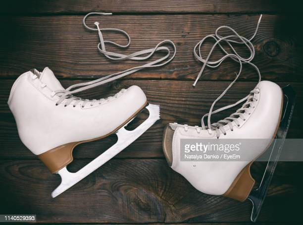 directly above shot of ice skates on wooden table - ice skate stock pictures, royalty-free photos & images