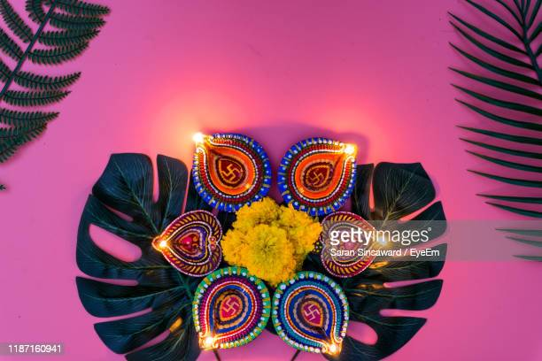directly above shot of illuminated diyas against pink background - diwali decoration stock pictures, royalty-free photos & images