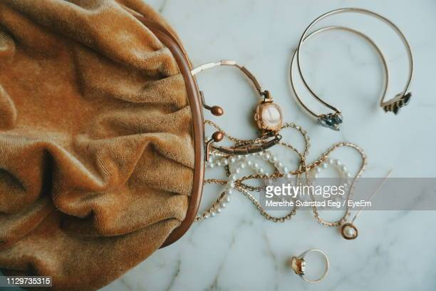 directly above shot of jewelry by purse on table - イヤリング ストックフォトと画像