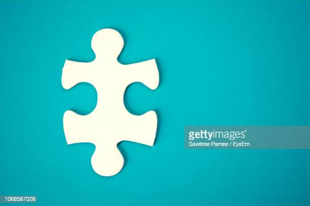 directly above shot of jigsaw piece over blue background - jigsaw piece stock pictures, royalty-free photos & images