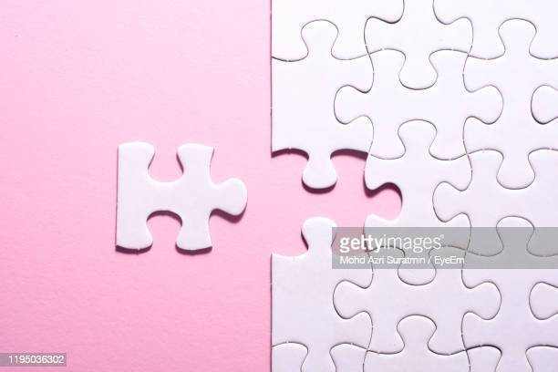directly above shot of jigsaw pieces over pink background - incomplete stock pictures, royalty-free photos & images