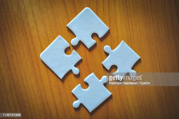 directly above shot of jigsaw puzzle pieces on wooden table - four objects stock pictures, royalty-free photos & images