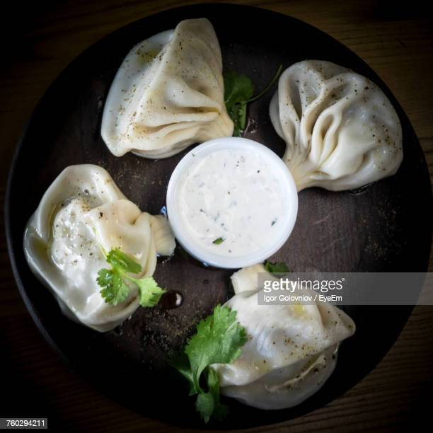 directly above shot of khinkali with dip served in plate on wooden table - igor golovniov stock pictures, royalty-free photos & images