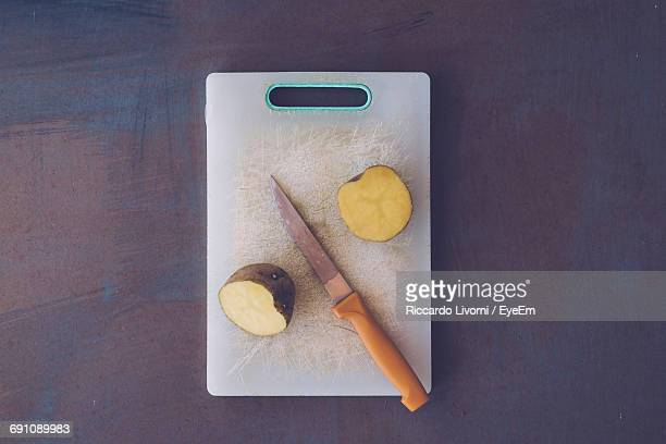 Directly Above Shot Of Kitchen Knife By Halved Potato On Cutting Board At Table