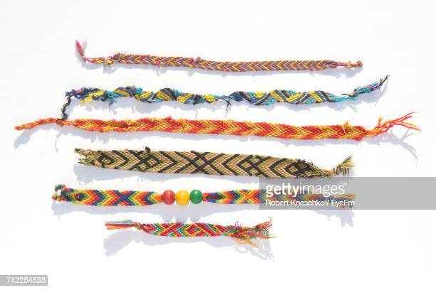 directly above shot of knitted bracelets on white background - brazalete pulsera fotografías e imágenes de stock