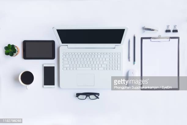 directly above shot of laptop and offices supplies on white background - blank laptop stock pictures, royalty-free photos & images
