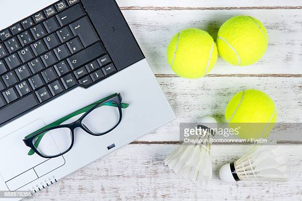 Directly Above Shot Of Laptop With Eyeglasses And Sports Equipment On White Table