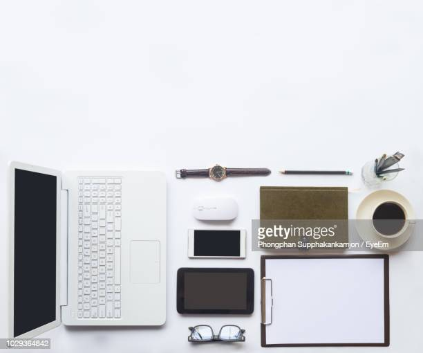 directly above shot of laptop with office supplies over white background - accessoires stock-fotos und bilder