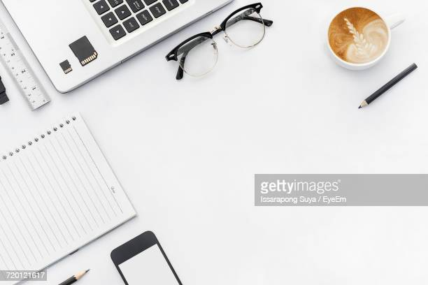Directly Above Shot Of Latte With Technology And Office Supplies On White Table