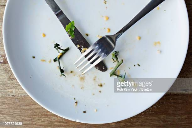 directly above shot of leftovers with fork and knife on table - leftovers stock pictures, royalty-free photos & images