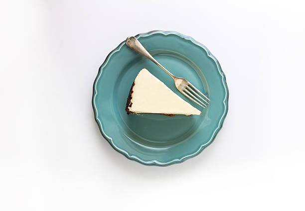 directly above shot of lemon cheesecake in plate on white background - 芝士蛋糕 個照片及圖片檔