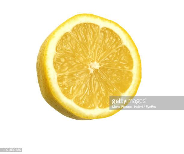 directly above shot of lemon slice against white background - lemon stock pictures, royalty-free photos & images