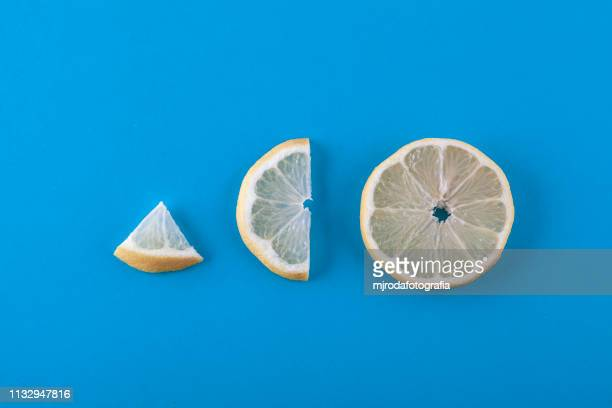 directly above shot of lemon slices on blue blackground - fruta stock photos and pictures