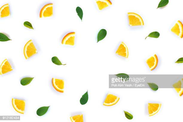 directly above shot of lemon slices with herbs over white background - zitrone stock-fotos und bilder