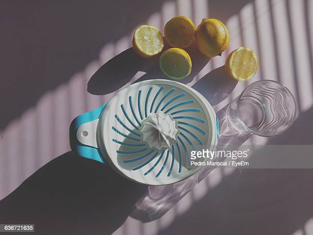 Directly Above Shot Of Lemons With Squeezer On Table