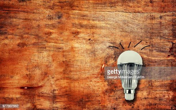 Directly Above Shot Of Light Bulb On Wooden Table