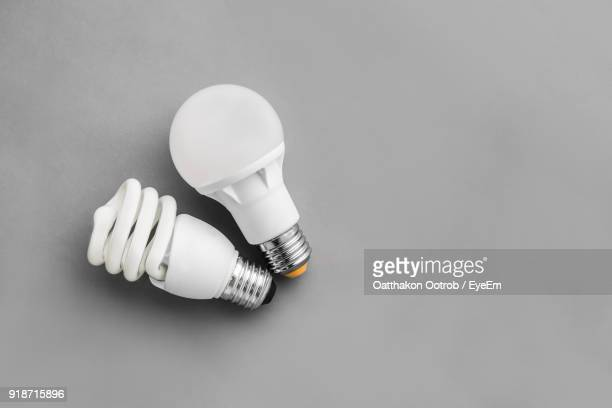 directly above shot of light bulbs over gray background - energy efficient lightbulb stock photos and pictures