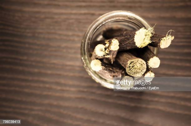 Directly Above Shot Of Liquorice Roots In Container On Wooden Table