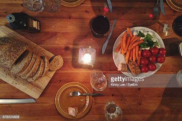 Directly Above Shot Of Lit Candle Amidst Food Served On Table At Home
