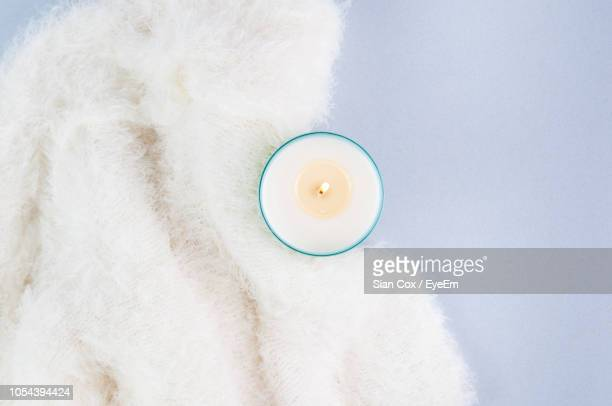 directly above shot of lit tea light candle by wool over gray background - ローソク ストックフォトと画像
