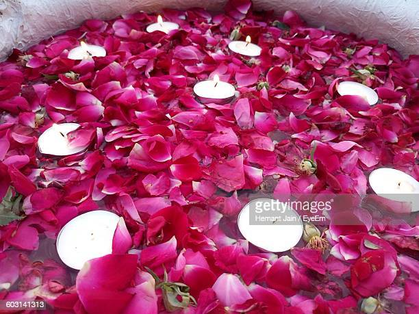Directly Above Shot Of Lit Tea Light Candles Amidst Rose Petals