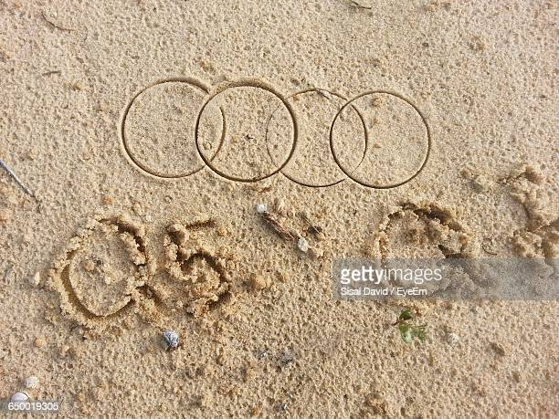 Directly Above Shot Of Logo Drawn On Sand At Beach