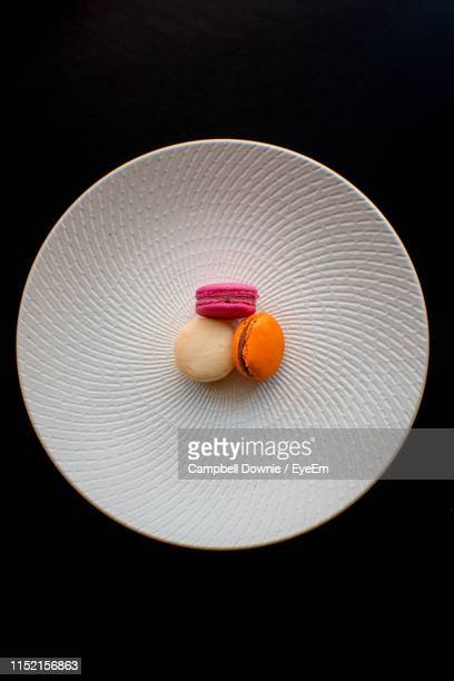 directly above shot of macaroons in plate over black background - campbell downie stock pictures, royalty-free photos & images