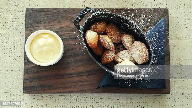 Directly Above Shot Of Madeleine Sponge Cake In Container On Wood At Table
