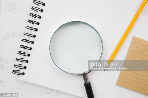 directly above shot of magnifying glass on paper on table - spiralblock stock-fotos und bilder