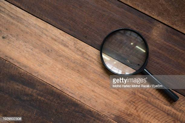 directly above shot of magnifying glass on table - magnifying glass stock pictures, royalty-free photos & images