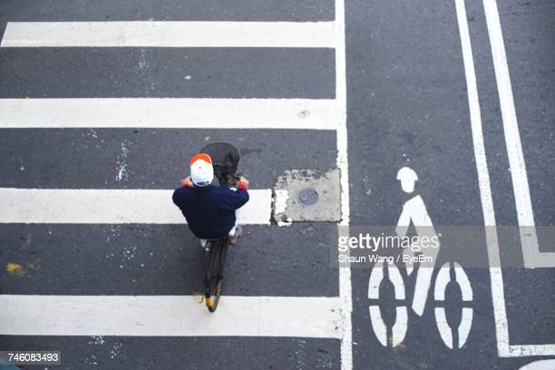 Directly Above Shot Of Man Cycling On Bicycle Lane