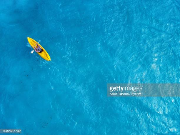 directly above shot of man kayaking in sea - kajak stock-fotos und bilder
