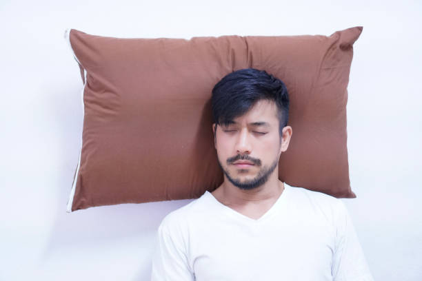 directly above shot of man sleeping on pillow against white background - sleep with elevated head stock pictures, royalty-free photos & images