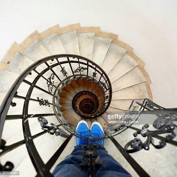 Directly Above Shot Of Man Standing At Railing Of Spiral Staircase