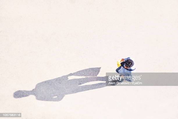 directly above shot of man walking on road - schaduw stockfoto's en -beelden