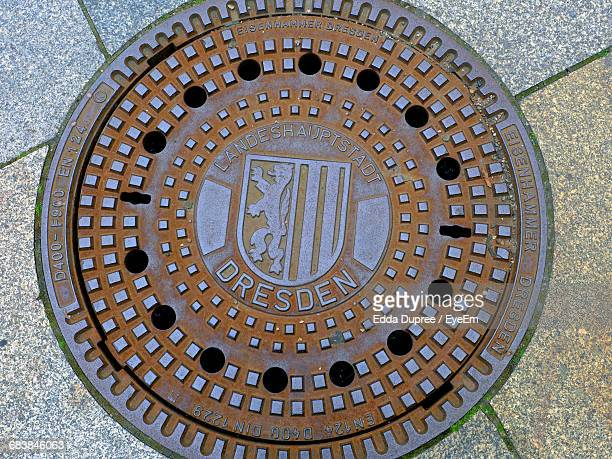 Directly Above Shot Of Manhole With Text On Street