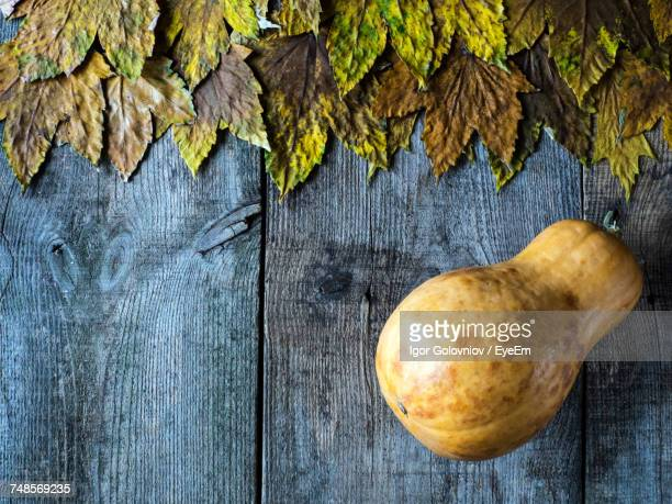 directly above shot of maple leaves with pumpkin on wooden table - igor golovniov stock pictures, royalty-free photos & images