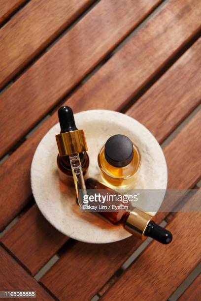 directly above shot of massage oil in bowl on table - aromatherapy stock pictures, royalty-free photos & images