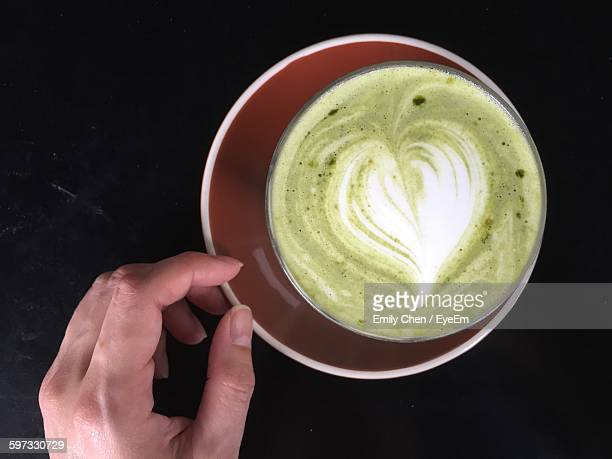 Directly Above Shot Of Matcha Latte In Cup With Cropped Woman Hand