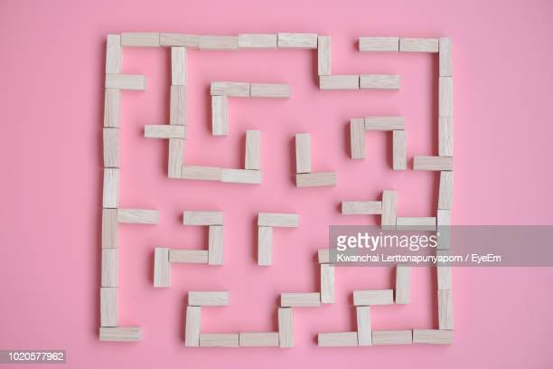directly above shot of maze made with wooden toy blocks against pink background - maze stock photos and pictures