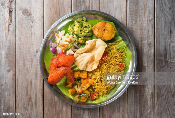 directly above shot of meal served in plate on wooden table - indian food stock pictures, royalty-free photos & images