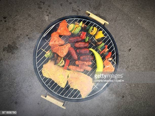 directly above shot of meat and vegetables on barbecue grill - grill concept stock photos and pictures