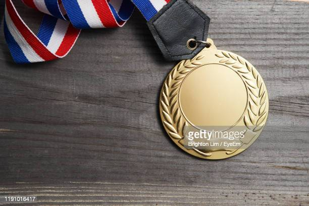 directly above shot of medal on wooden table - trophy stock pictures, royalty-free photos & images