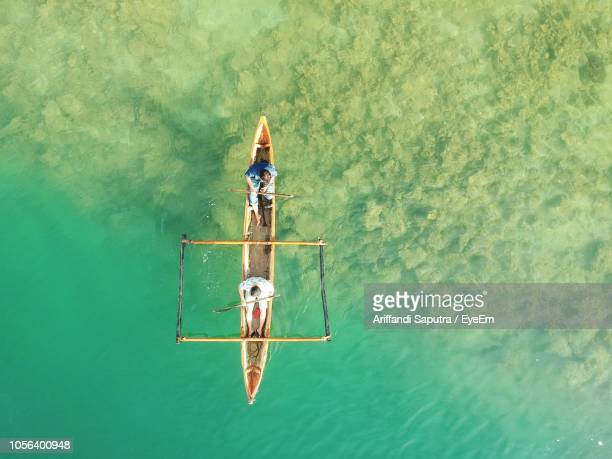 directly above shot of men on longtail boat sailing in sea - asiatisches langboot stock-fotos und bilder
