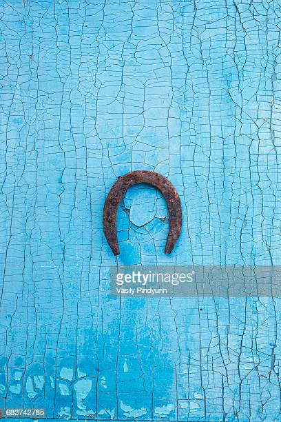 Directly above shot of metallic rusty horseshoe on old blue table