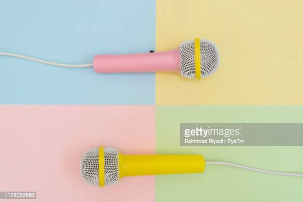 directly above shot of microphones on colored background - micro photos et images de collection